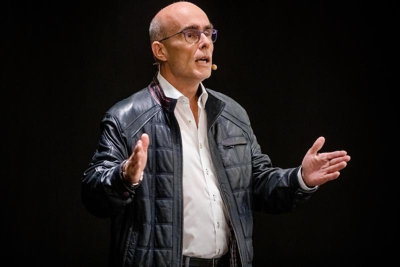 Speaker erklärt auf einer Bühne mit offenen Armen