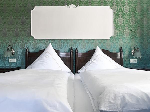 Hotelbett mit grüner Tapete